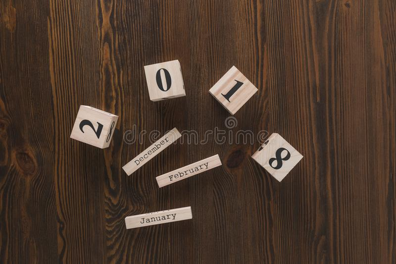 Top view of parts of wooden calendar on dark. Wooden tabletop stock image
