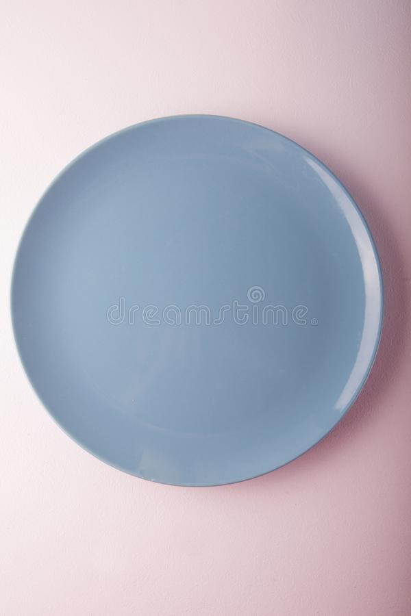 Top view of a pastel blue plate on a pastel peach background. Minimalism food photography. Geometric style. Copy space royalty free stock images