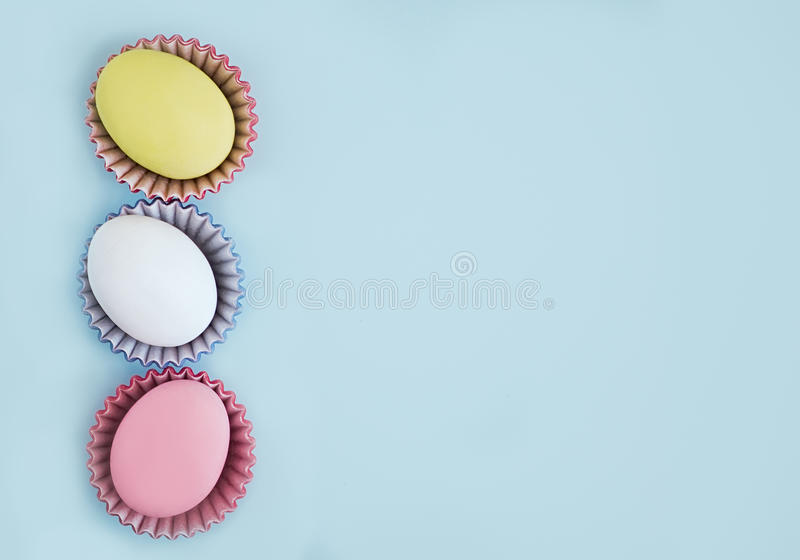 Top view pastel colors eggs row on a blue background royalty free stock photo