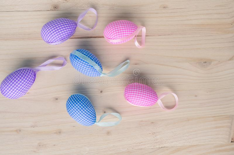 Top view of pink and blue checkered Easter eggs decorations  on pale wooden background stock image