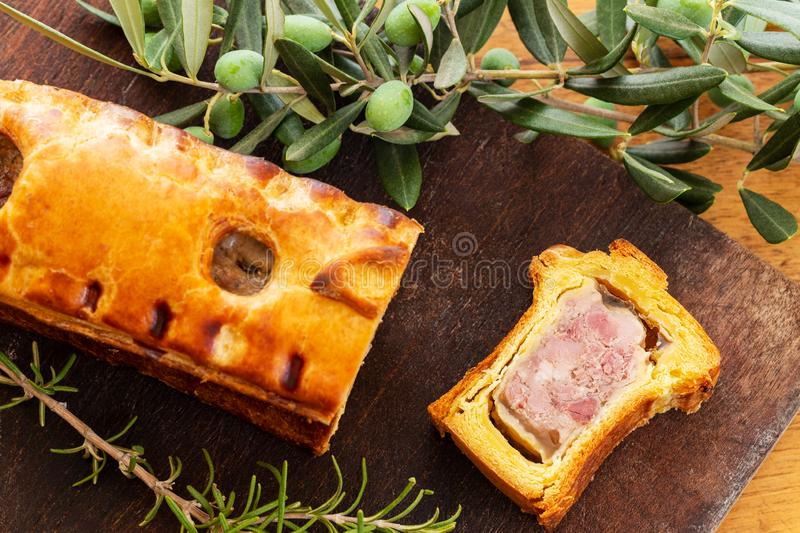 Top view of a pate en croute or pâté en croûte with rosemary twig and green olives branch over a dark wooden cutting board. Top view of a pate en stock photography