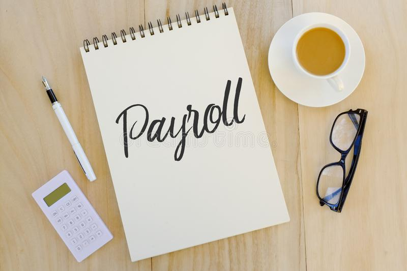 Top view of pen,calculator,glasses,acup of coffee and notebook written with Payroll on wooden background. stock photos