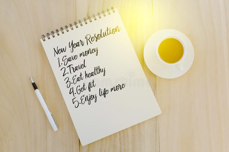 Top view of pen,a cup of coffee and notebook written with list of New Year Resolutions. New Year concept. stock photo