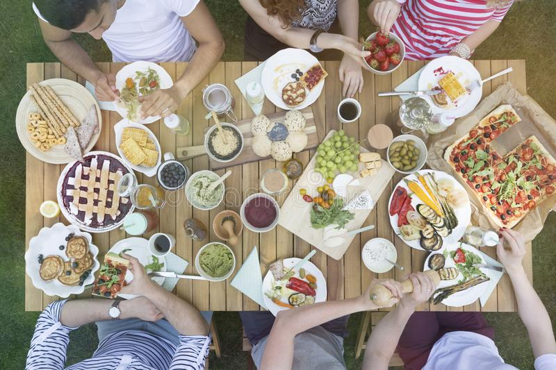 Top view on people eating lunch on wooden table in the garden stock photos