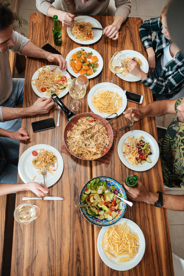 Top view of people having dinner together while sitting. Top view of group of people having dinner together while sitting at the rustic wooden table at home stock photography