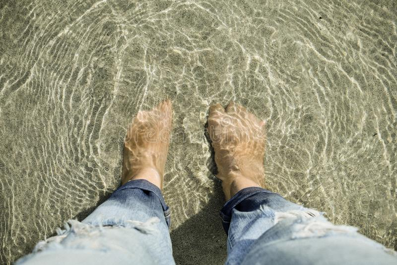 Top view of people looking down at feet put under sand and sea. At thailand beach royalty free stock photo