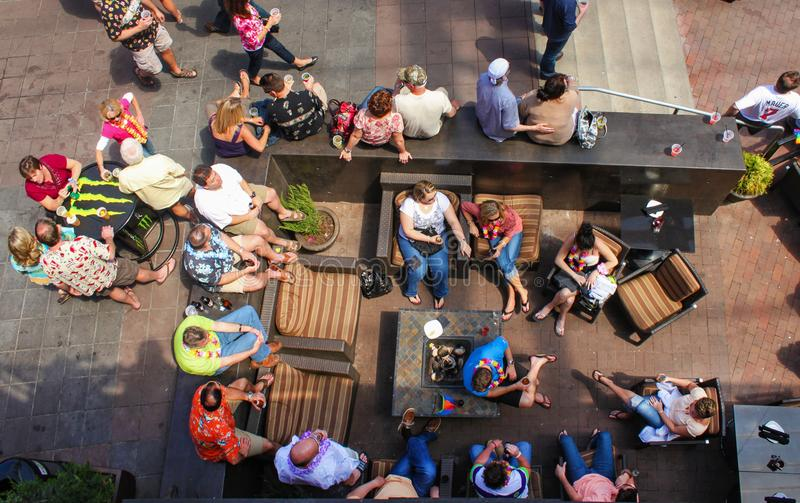 Top view of people sitting around with summer clothing and leis and drinks in an outside sitting area and at tables at P&L Distric stock images