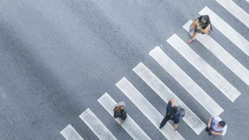 From the top view of people walk on street pedestrian crossroad. In the city street with the motorcycle drives pass road ,bird eye view stock photo