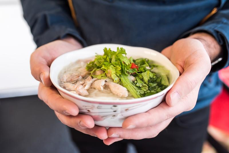 Pho ga soup with the serving sauces, herbs and spices royalty free stock image