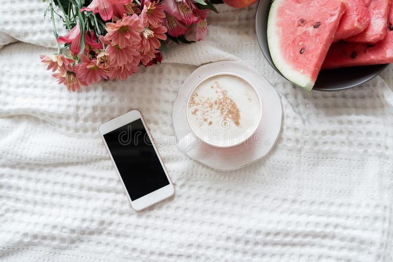Top view of phone and coffee on the female bed. Flat lay, copy s royalty free stock images
