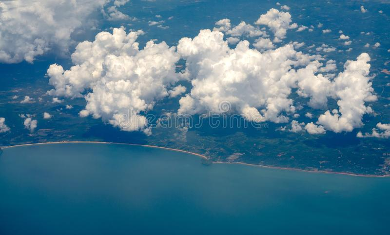 Top view photo from airplane overlooking the clouds, the coastline and the island with beautiful blue-green sea water stock photos