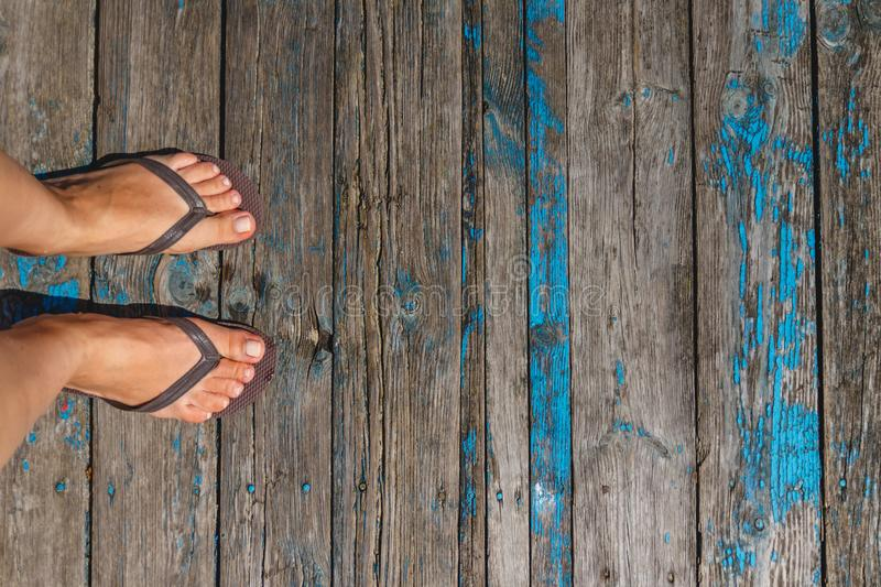 Top view, photo of female legs in beach flip flops on a wooden old floor. Photos on vacation, beach, summer stock photography