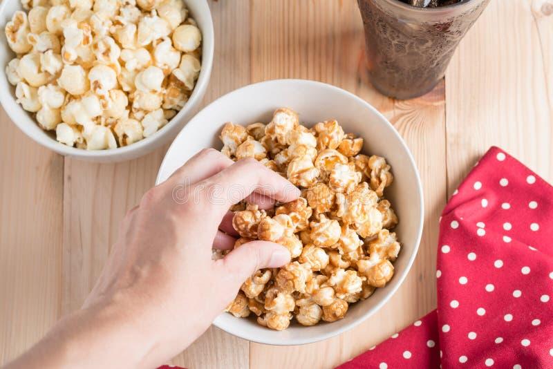 Top view photo of women hand eating popcorn. stock photo