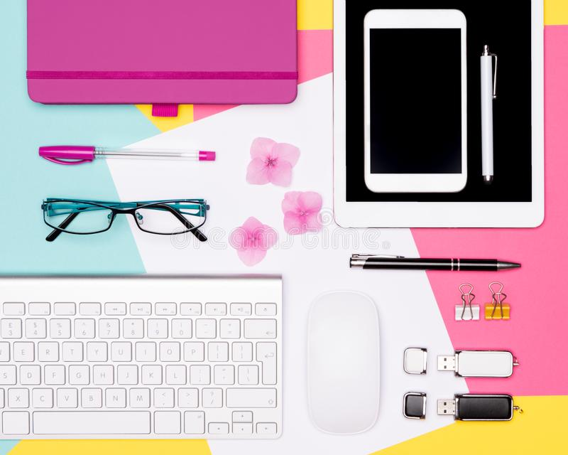 Top view photo of workspace with blank mock up tablet and smartphone, coffee cup, keyboard, and notepad on pastel background. royalty free stock images