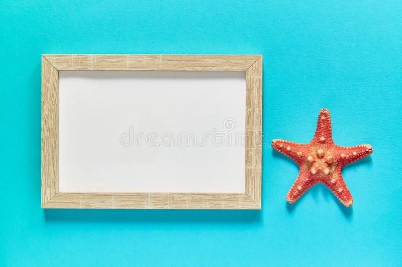 Top view of photoframe with seashells and starfish on blue background. Summer vacation concept. Sea flat lay royalty free stock photography