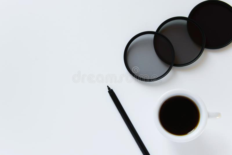 Top view of photography work desk. Flat lay workspace with photographic filters, cup of coffee and pen on white background. Minimal, black and white tones and stock photos