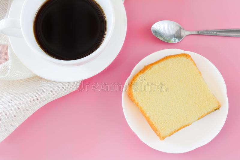 Top view piece of butter cake on white dish served with cup of black coffee, metal spoon. Times to relax concept. Background, baked, bakery, bread, breakfast royalty free stock images