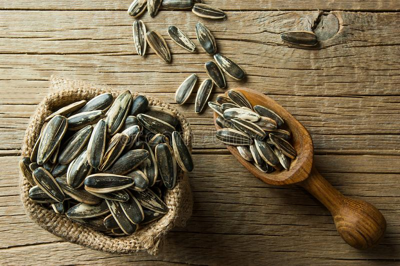 Top view Pile, heap of roasted sunflower seeds in burlap sack and shovel on wooden table stock photography