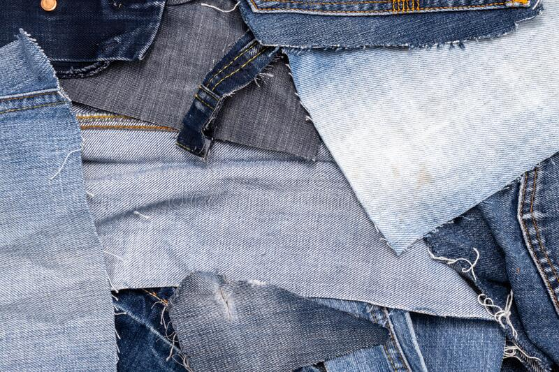 Top view of a pile of scraps of old blue jeans stock image