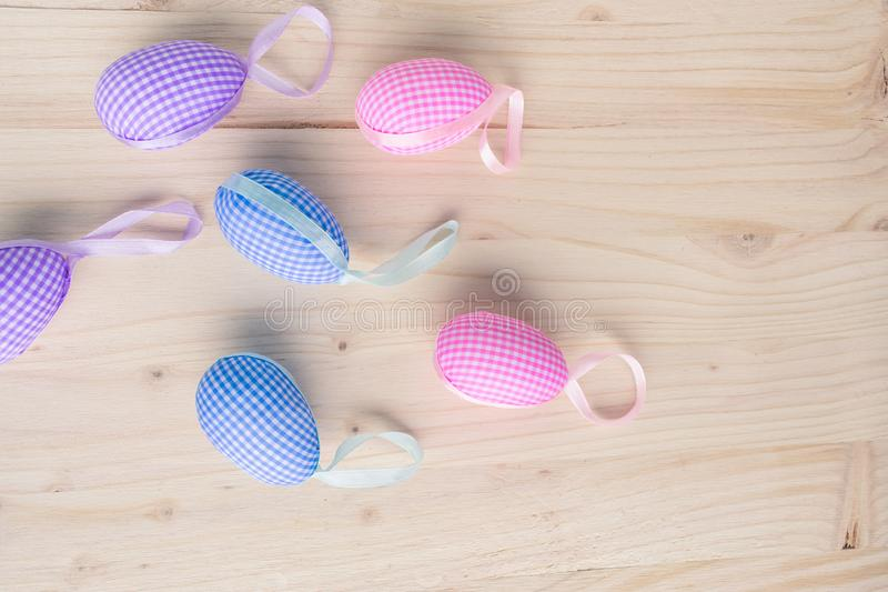 Top view of pink and blue checkered Easter eggs decorations  on pale wooden background royalty free stock image