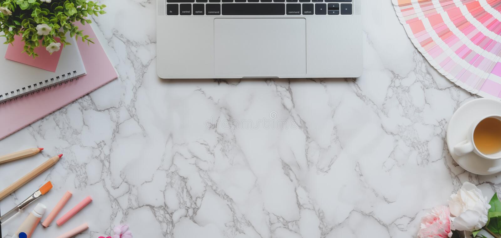 Top view of pink feminine designer workspace with laptop computer and painting tools on marble desk royalty free stock images