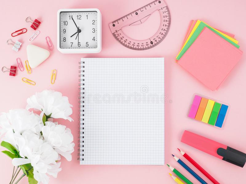Top view of pink office desktop with notebook in cage, flowers, royalty free stock photos