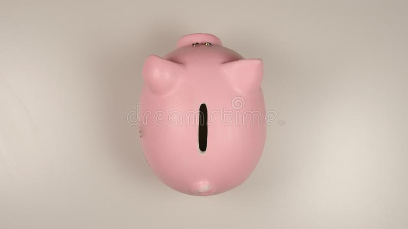 TOP VIEW: Pink pig money box on a white table stock image