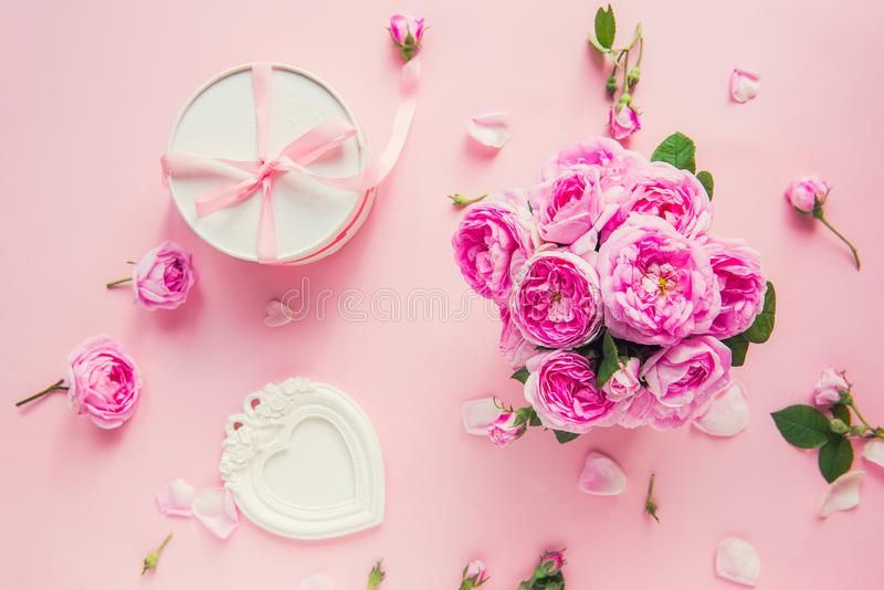 Top view pink tea roses bouquet, white round box with ribbon and vintage photo frame in shape of heart on pink background. Festive royalty free stock image