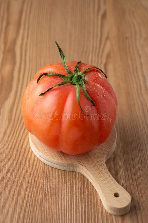 Top view of a pink tomato with water drops on small table and wooden table in vertical stock photo