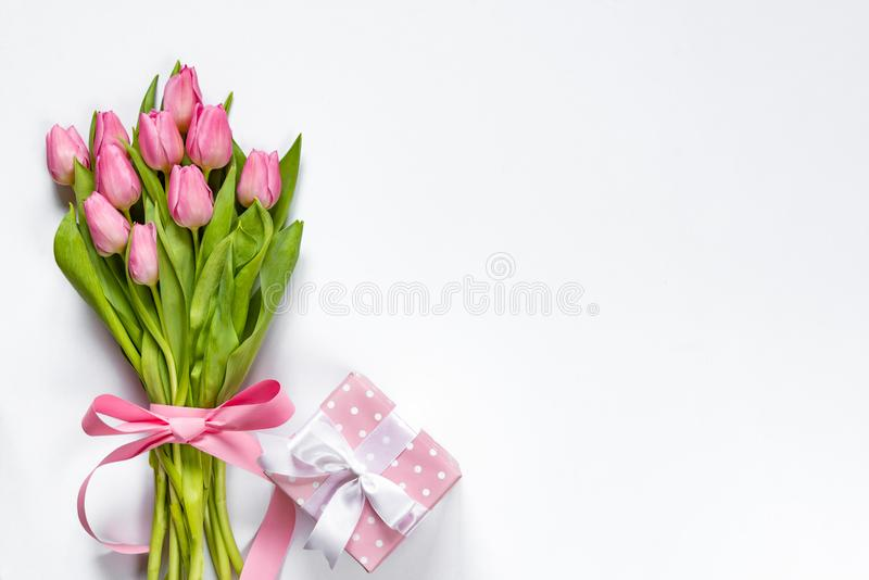 Top view of pink tulips bouquet, wrapped with pink ribbon and pink dotted gift box over white background. Copy space. royalty free stock photography