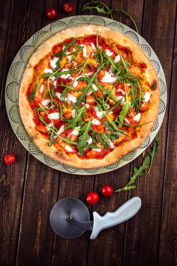 Top view Pizza Margherita with Buffalo mozzarella, tomatoes and fresh basil. Pizza cutter lies on the wooden background. Vertical royalty free stock images
