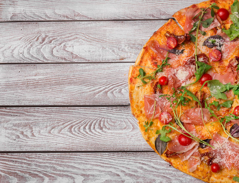 Top view of a pizza. Pizza with meat, cheese and vegetables on a wooden background. Italian cuisine concept. Copy space. stock photography