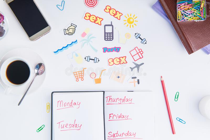 Top view Planning Organizer mark up for a week and colourful icons of actions on the working place with stationery and coffee. Cre royalty free stock photo