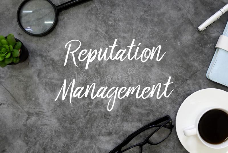 Top view of plant,magnifying glass,pen,notebook, a cup of coffee and sunglasses on grey grunge floor written with Reputation. Management, online, media, social stock photography