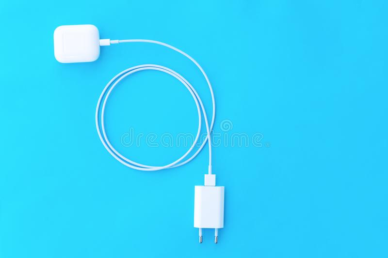 Top view plastic white wireless headphones for smartphone, charging case, Lighning USB, adapter on a pastel blue background. Copy stock photos