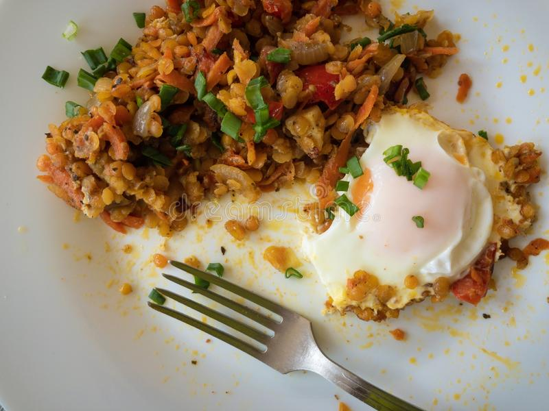 Top view on plate with fried egg, red lentil baked with vegetables. Half eaten stock images