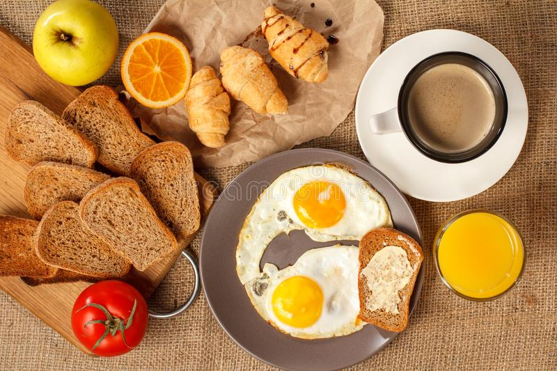 Plate with fried eggs, glass of orange juice, cup of black coffee, croissants, bread on wooden cutting board, fresh tomato, apple royalty free stock photography