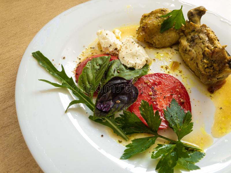 Plate with fried pieces of chicken, red sliced tomatoes, soft cheese, branch of arugula, parsley and basil leaves stock photography