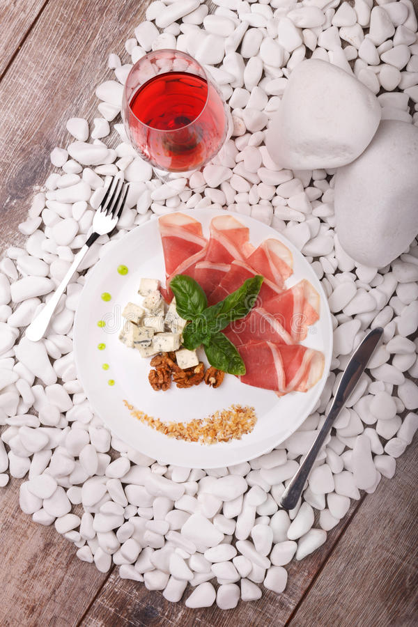 Top view of a plate with prosciutto, Roquefort cheese, walnuts and basil, a glass of red wine on a white stone wooden royalty free stock images