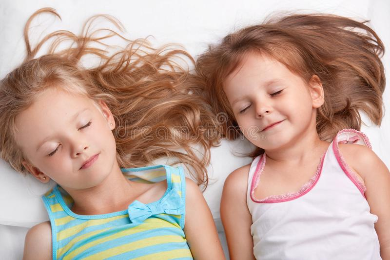Top view of pleased attractive small girls or sisters smile together, sleep in bed, lie closely to each other, see pleasant dreams stock photo