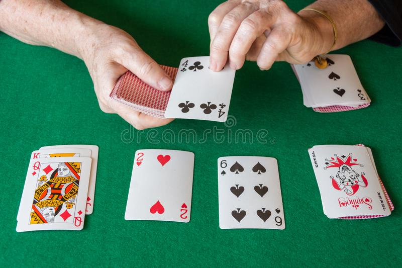 Top view of poker cards on green mat with woman`s hands playing solitaire. Horizontal royalty free stock photos