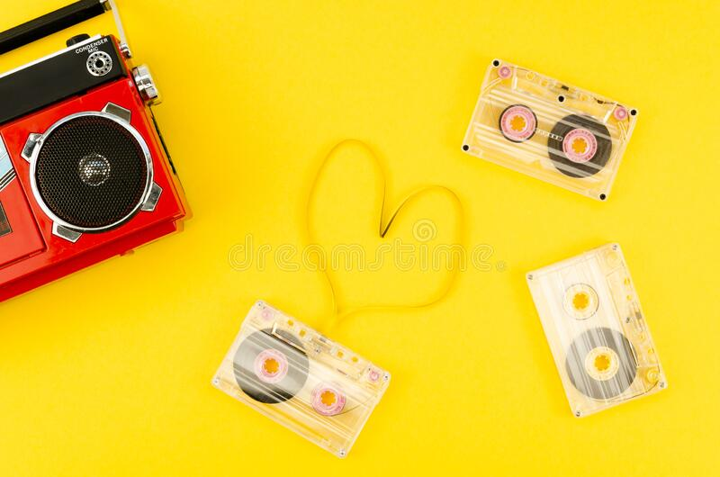 Top view pop vintage red radio with a cassette tape in shape of a heart on a yellow background. Music lover concept royalty free stock photo