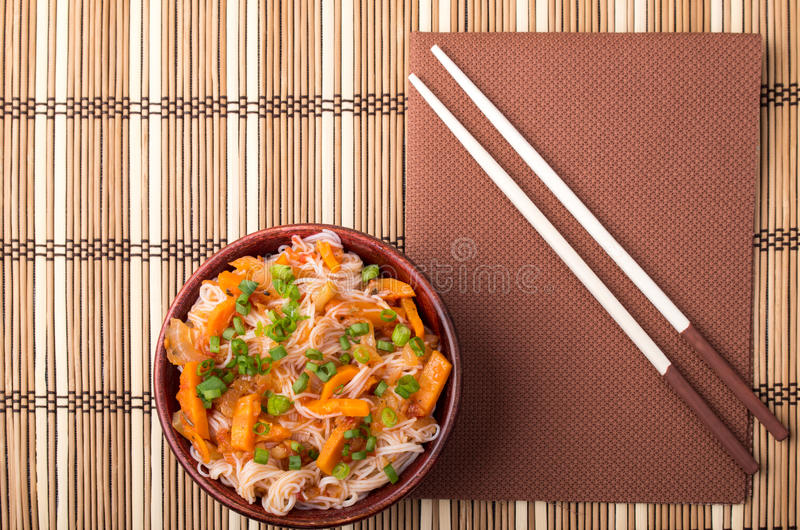 Top view on a portion of rice vermicelli hu-teu in a small brown. Top view on a portion of rice vermicelli hu-teu with vegetable carrot sauce in a wooden bowl stock photo
