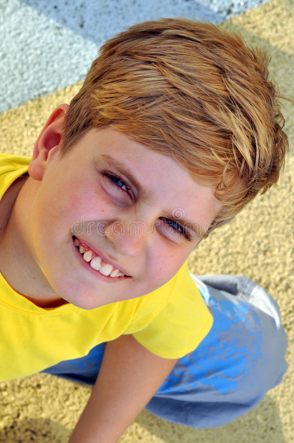 Top view portrait of a blond boy showing his teeth