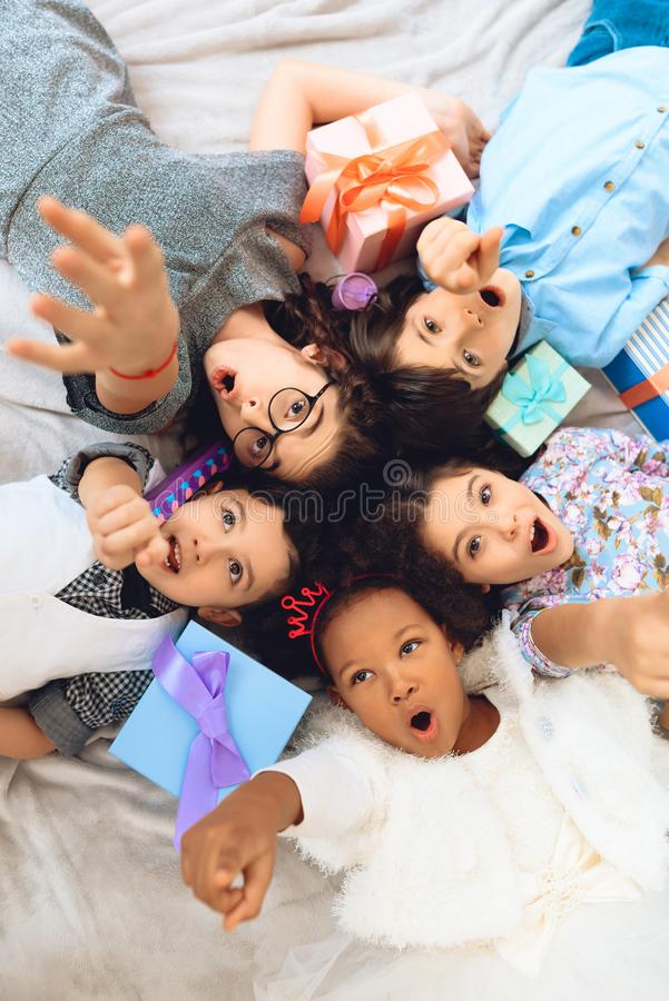 Top view. Portrait of happy children who lie on floor in shape of circle. stock image