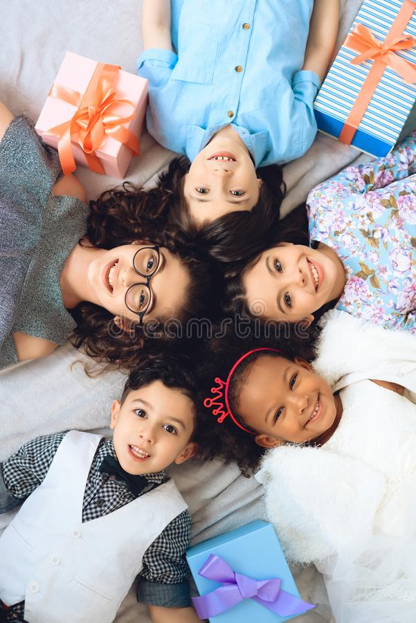 Top view. Portrait of happy children who lie on floor in shape of circle. stock images