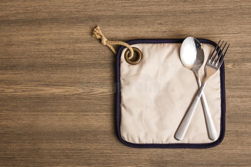 Stainless spoon and fork. Top view portrait of stainless spoon and fork on wooden table with copy space stock image