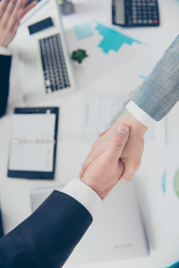 Top view portrait of two elegant classic partners making handshake above signed contract in work place, workstation royalty free stock image