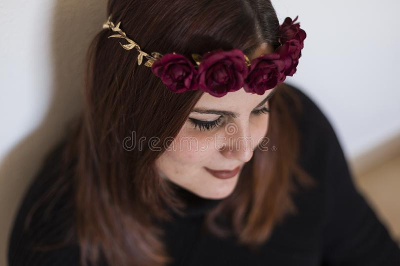 Top view portrait of a young beautiful woman wearing a red roses wreath. She is smiling, indoors. Lifestyle royalty free stock photo