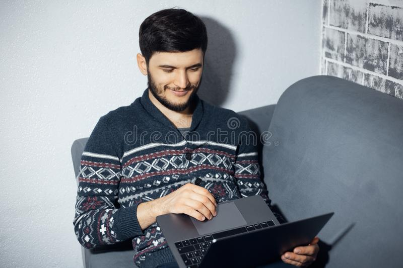 Top view portrait of young smiling man, sitting home on sofa, looking in laptop and using touchpad. stock photos